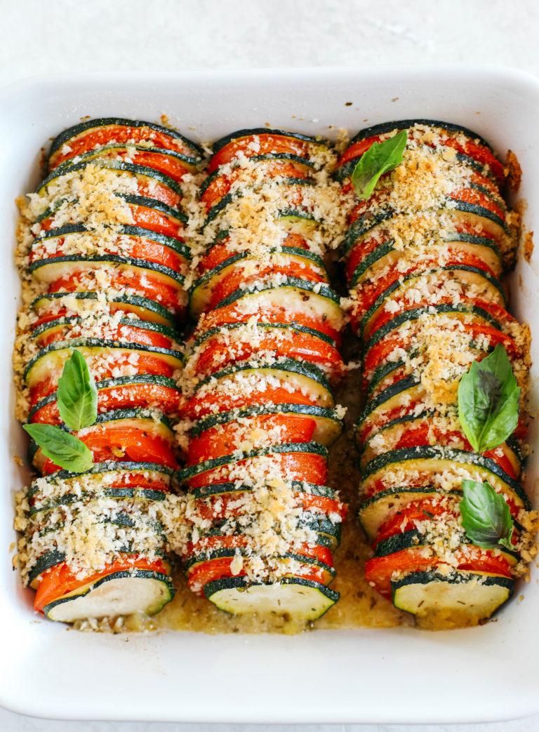 Este Gratinado de Calabacín y Tomate de Verano está lleno de capas de deliciosas verduras, todo cubierto con una cubierta de hierba crujiente y cursi que se hornea a la perfección.