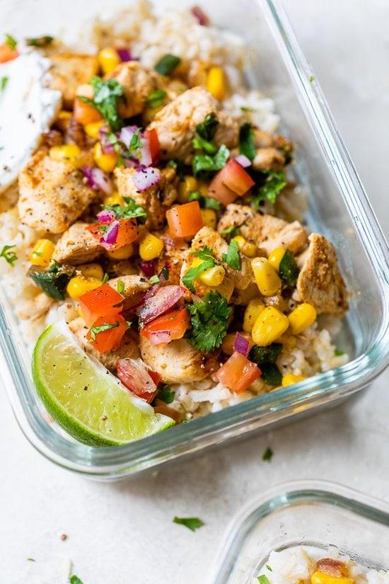 Tazones de arroz con pollo y taco poblano en un recipiente de vidrio para preparar comidas.